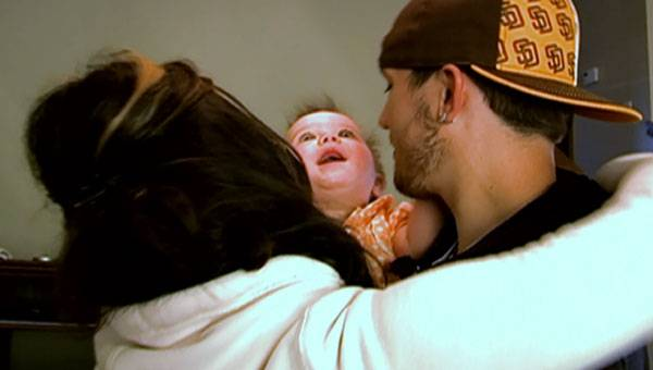 Baby Aubree gets a big hug from mom and dad.