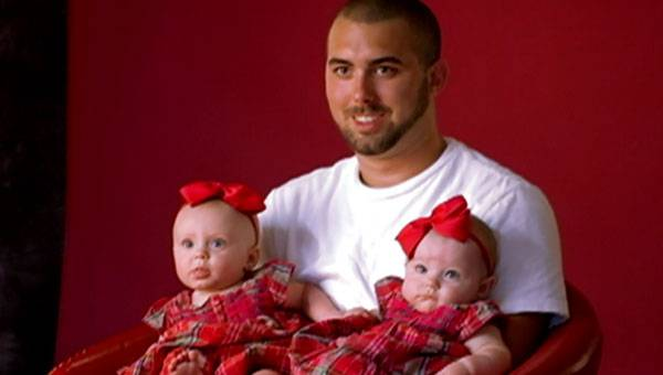 Corey poses for a photo with his twin girls.