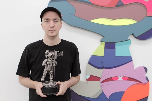 Brooklyn artist KAWS holding the reimagined VMA Moonman.