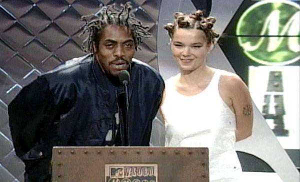A VMA double-take! Presenters Coolio and Björk look like twinsies as they hit the stage with matching manes in 1994.