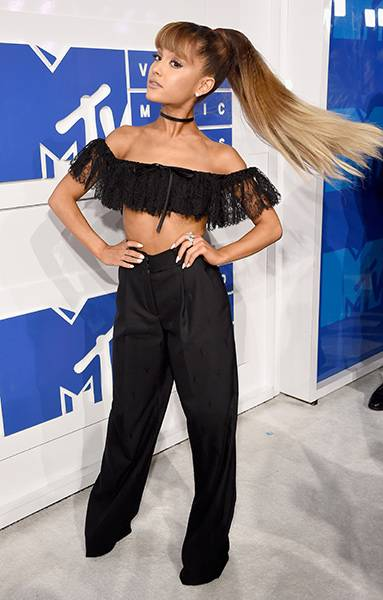 Ariana Grande whips her signature ponytail while rocking a playful lace crop top and dress pants on the 2016 VMA Red Carpet.