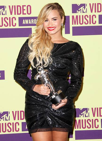 """Demi Lovato is presented with her 2012 Moonman for Best Video With A Message after her Pre-Show performance of """"Give Your Heart A Break."""""""