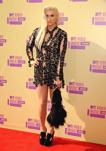Ke$ha keeps it classy in a black, long-sleeved mini-dress complete with flirty flower embellishments on the 2012 VMA red carpet.