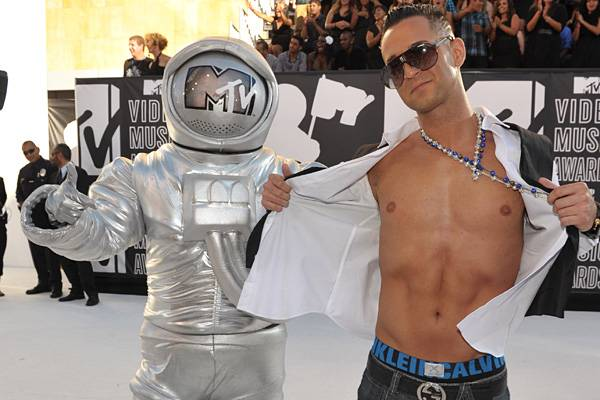 """'Jersey Shore' star Mike """"The Situation"""" shows off his infamous abs next to the Moonman at the 2010 VMAs."""