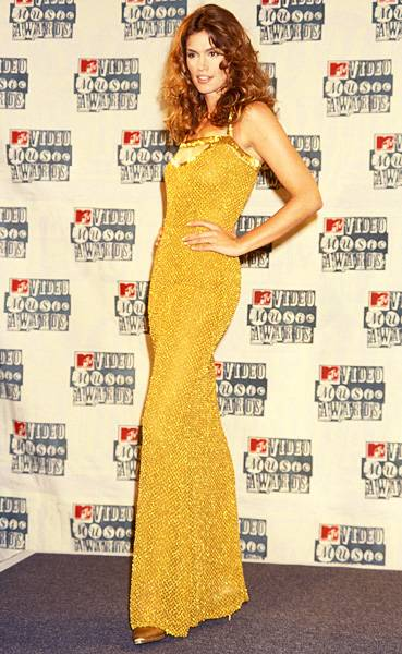 Cindy Crawford of 'House of Style' shows off her svelte figure in a golden masterpiece of a dress at the 1994 MTV Video Music Awards.