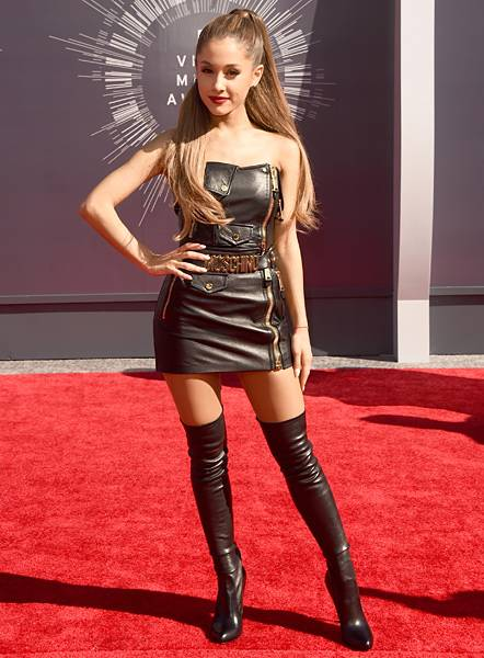 Ariana Grande arrives on the 2014 red carpet in a skin-tight black leather dress paired with over-the-knee matching boots.