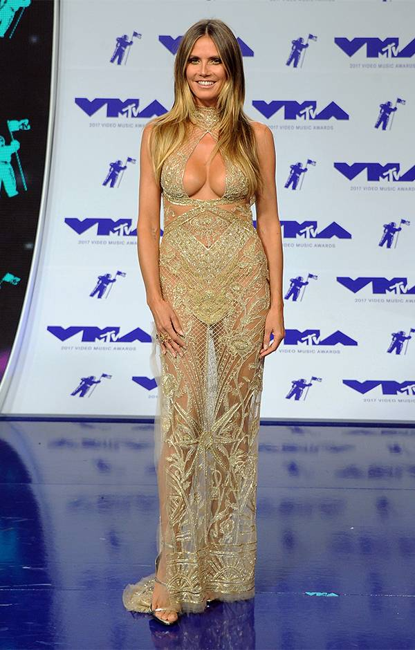 Supermodel Heidi Klum was a golden goddess at the 2017 VMAs, showing off her tan under this shimmering lace gown.