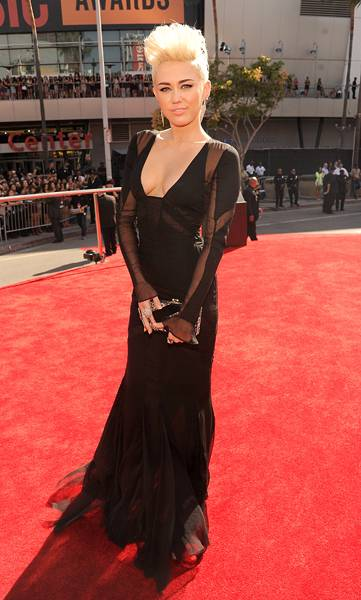 Miley Cyrus debuts her new 'do and banging bod in a black gown with sheer detailing n the 2012 VMA red carpet.