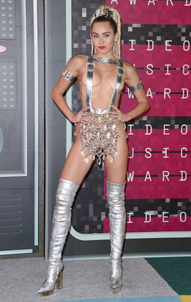 Hostess-with-the-mostess Miley Cyrus hit the 2015 VMA red carpet in an eye-popping silver ensemble. Suspenders and chandeliers, anyone?
