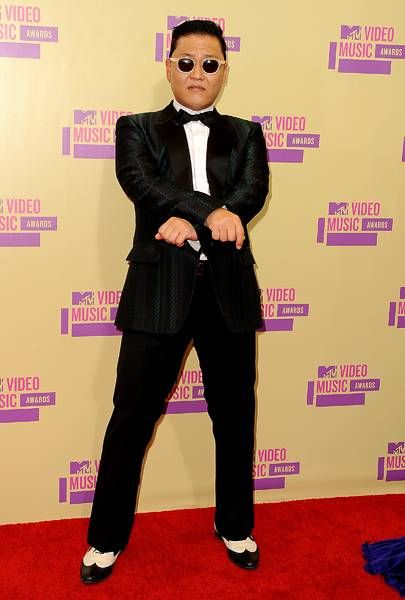 PSY celebrates his signature strut in a snazzy black suit on the 2012 VMA red carpet.