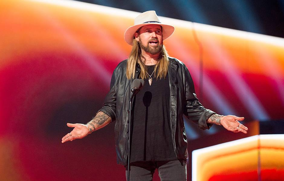 Billy Ray Cyrus dons a leather jacket and his signature cowboy hat.