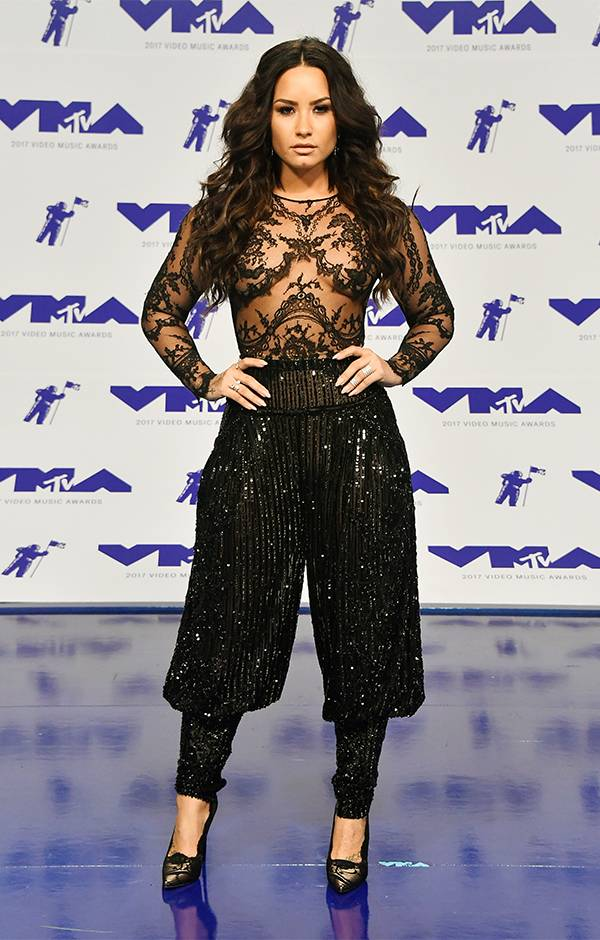 Demi Lovato slayed the 2017 VMA red carpet pairing a revealing black lace top with black sequin pants.