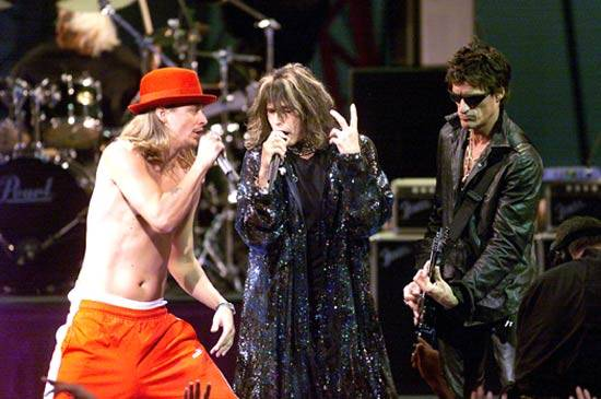 """Kid Rock, Aerosmith and Run DMC (not pictured) perform """"Walk This Way"""" on stage at the 1999 Video Music Awards in New York City."""