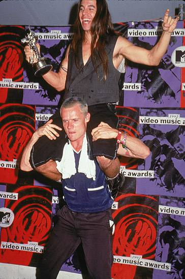 Flea and Anthony Kiedis of Red Hot Chili Peppers add the Moonman to the top of their Best Breakthrough Video totem pole at the 1992 MTV Video Music Awards.