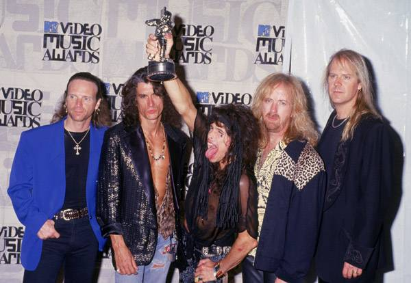 After the 1993 MTV Video Music Awards, Aerosmith's Steven Tyler opens up wide and prepares to swallow the band's Moonman.