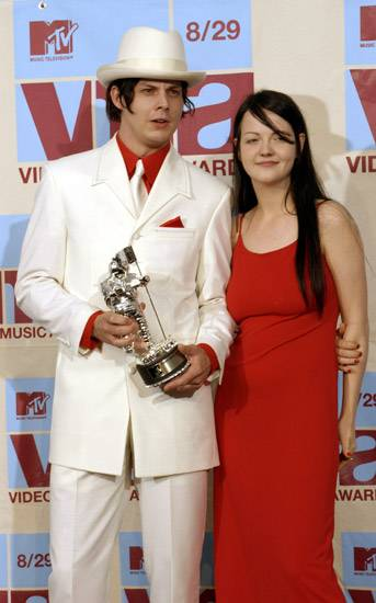 Jack and Meg of The White Stripes pose simply with their Moonman to match the elegant prom-night pose they're rocking at the 2002 MTV Video Music Awards.