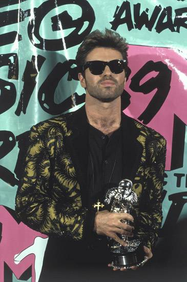 George Michael keeps his sunglasses on at the 1989 MTV Video Music Awards to counter the gleam of his Moonman.
