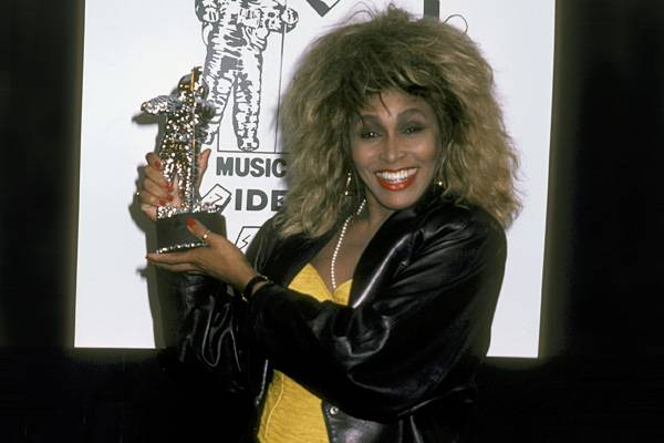 At the 1986 VMAs, Singer Tina Turner happily shares with us her Moonman for Best Stage Performance with Bryan Adams.