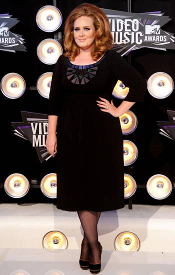 Adele looks elegant in a simple black cocktail dress, spiced up with geometric bib detailing on the 2011 VMA red carpet.