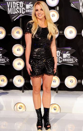 Britney Spears rocks head-to-toe black in a playful black romper with sequined stripes and scalloped edges at the 2011 VMA red carpet.
