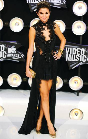 Selena Gomez steals the show in a sexy and sophisticated black dress with layered lace cut outs and a dramatic train on the 2011 VMA red carpet.