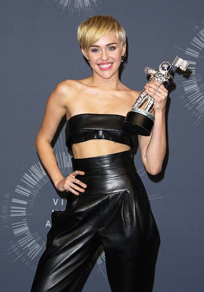 Miley shows off her midriff, megawatt smile and 2014 Video Of The Year Moonman.