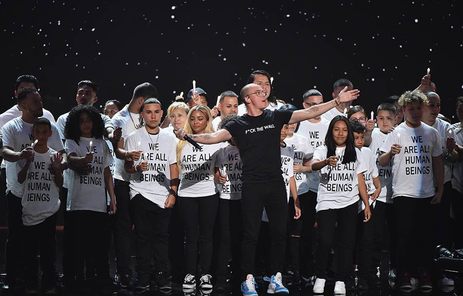 """Logic and Ryan Tedder perform """"One Day"""" with immigrant families at the center of their performance on stage sending a powerful message at the 2018 VMAs."""